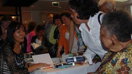 Griselda Molemans signeert haar thriller 'Tot op het Bot' op de Tong Tong Fair in Den Haag.